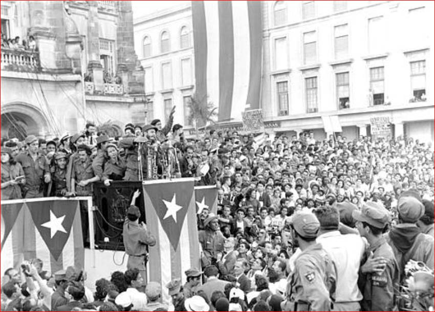 A black and white photograph of Fidel Castro giving a speech to a large crowd in 1959.