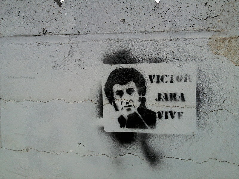 "Street art of Victor Jara's face with the words ""Victor Jara lives"" next to it."
