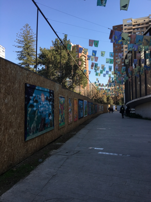 murals and hanging signs along pathway to museum