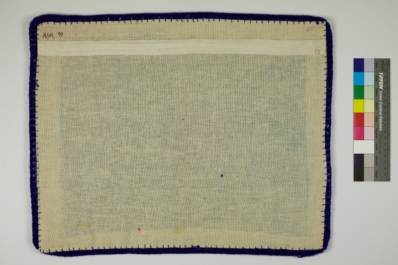 The back of an Arpillera lined with blue yarn