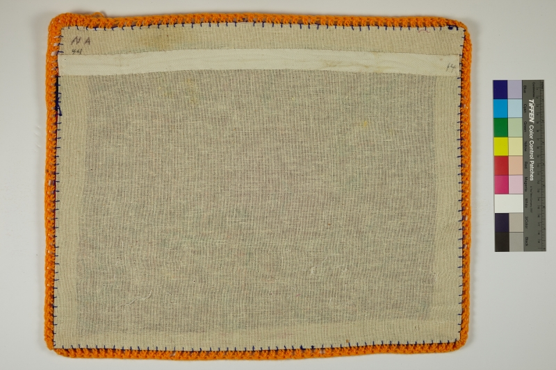 The back of an Arpillera lined with orange yarn